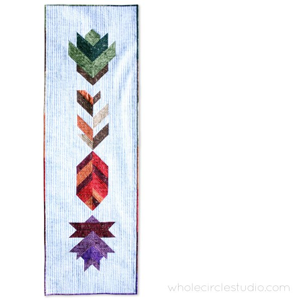 A fun, modern autumn wall hanging quilt or table runner! Leaf Peepers is a modern spin on the traditional half square triangle block. Join the sew along and quilt along and make this for your home or as a gift for Thanksgiving! Leah Day and Whole Circle Studio will walk you through all of the steps of this PDF pattern on their blogs. Add additional background fabric to make a larger quilt!
