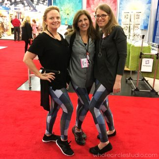 Showing off our Hexie Blues Leggings (pants that look like a quilt—but it's not!). Sheri of Whole Circle Studio with Just Wanna Quilt — Quilt Army members at International Quilt Market 2018 in Houston, Texas