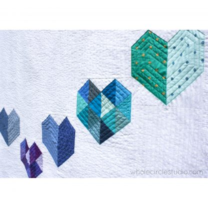 detail of rainbow, scrap version of Love at First Sight — an easy, beginner-friendly foundation paper piecing quilt pattern and makes the perfect wedding, engagement, anniversary or friendship gift. It's also super sweet for a baby or kid. Included in the pattern are instructions for two types of heart blocks—basic and details along with fabric requirements and instructions to arrange the blocks into 3 layouts—a wall quilt or two types of throw quilts. Make it your own by swapping out fabric or rearranging the blocks.