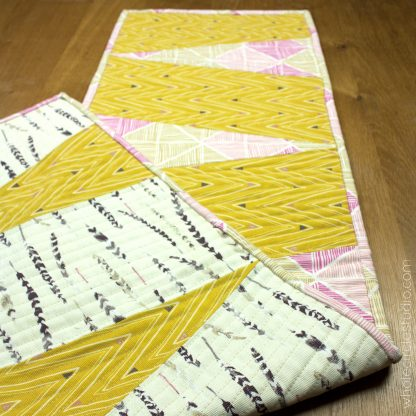 Dress up your table with this reversible, easy to make runner! Piece and quilt with the supplied templates. Makes a great hostess gift! Designed by Whole Circle Studio.