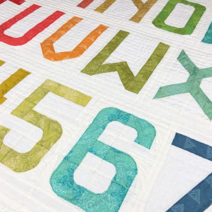 detail of Alphabet quilt made with Typecast Fast, a Foundation Paper Piecing (FPP) Pattern Make all 26 letters of the alphabet, all the numbers and lots of punctuation — a total of 50 block designs! Pattern by Whole Circle Studio.