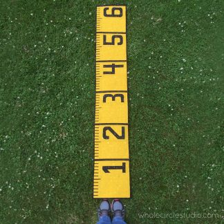 Make a social distancing quilt! This 6' Ruler quilt is a cheeky reminder in this time of social distancing of what six feet (or 2 yards for us quilters!) looks like. Make this tape measure quilt/runner as a utilitarian decoration for display and use at your next socially distanced gathering. When not being used for a utilitarian purpose, it also makes a fun table or bed runner. Make one as a gift a tinkerer, teacher, kid, or baby as a wall hanging or growth chart.